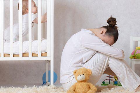 Мать сидит у детской кроватки