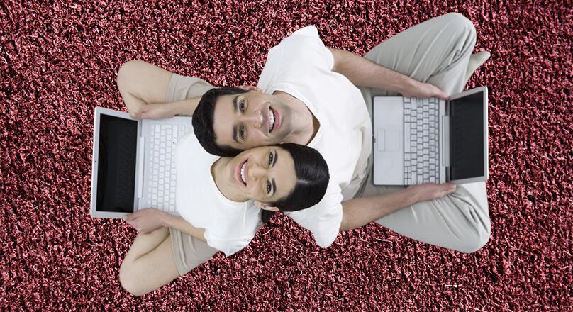 Девушка и парень сидят на полу с ноутбуками